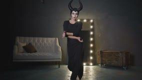 Dziewczyna w wizerunku Maleficent z wielkim czernią uzbrajać w rogi będący ubranym czarnego smokingowego tana i writhing zbiory wideo