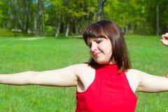 Dziewczyna w zielonej zielonej trawie i czerwieni Zdjęcia Stock