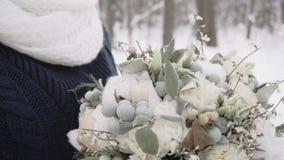Dziewczyna w zim mitynkach z pięknym bukietem kwiaty w zimnej śnieżnej pogodzie zbiory wideo