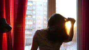 Dziewczyna wcześnie w ranek pozyci przy okno i czesze jej włosy Słońca ` s promienie przechodzą przez szkła iluminują zdjęcie wideo