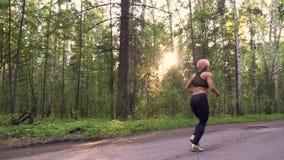 Dziewczyna wiąże koronki na sneakers i początku przecinającego kraju szkolenie w lesie zbiory wideo