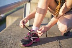 Dziewczyna Wiąże Shoelaces na Sneakers Fotografia Stock