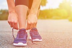 Dziewczyna wiąże up shoelaces w sneakers na drodze podczas gdy jogging, nogi i sneakers, Fotografia Royalty Free