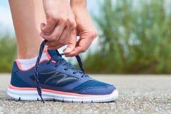 Dziewczyna wiąże up shoelaces w sneakers na drodze podczas gdy jogging, nogi i sneakers, Zdjęcie Stock