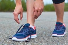 Dziewczyna wiąże up shoelaces w sneakers na drodze podczas gdy jogging, nogi i sneakers, Obrazy Royalty Free