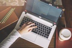 Dziewczyna wręcza działanie na nowożytnym laptopie Desktop, książka, pióro, kawa na tle obrazy royalty free
