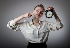 Dziewczyna wskazuje przy zegarem zegar o 5 Zdjęcia Royalty Free