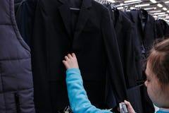 Dziewczyna wybiera czarną szkolną kurtkę w sklepie Zdjęcia Stock