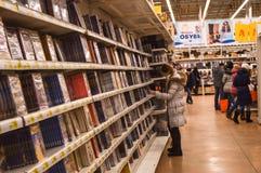 Dziewczyna wybiera książkę na półce Obraz Stock