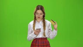 Dziewczyna wybiera numer liczby na telefonie z złoto kartą zielony ekran zbiory wideo