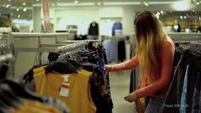 Dziewczyna wybiera odzieżowego w supermarkecie zbiory