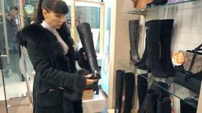 Dziewczyna wybiera w butik zimy butach zbiory