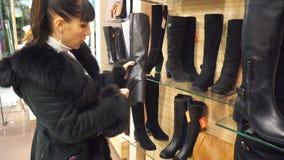 Dziewczyna wybiera w butik zimy butach zbiory wideo