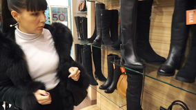 Dziewczyna wybiera w butik zimy butach zdjęcie wideo