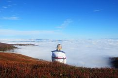Dziewczyna wycieczkowicza obsiadanie na rockowej górze relaksuje i inspiruje na wierzchołku himalajska góra, zdjęcia royalty free