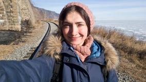 Dziewczyna Wycieczkuje na Baikal kolei w zimie Ciepło ubierający - szalik i kapelusz dziający, grżemy żakiet zdjęcia stock