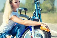 Dziewczyna wyciera jej motocykl z łachmanem obraz stock