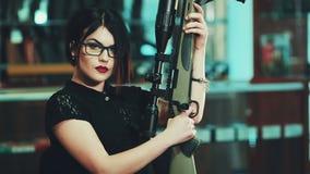 Dziewczyna z agresywnym spojrzeniem z snajperskim karabinem zdjęcie wideo