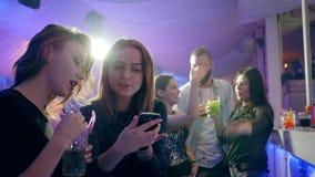 Dziewczyna z alkoholicznego napoju spojrzeniami przy ekranem dziewczyny ` s telefon komórkowy za zakazuje kontuar zbiory