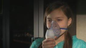 Dziewczyna z astma problemami robi inhalaci z maską na jej twarzy zbiory