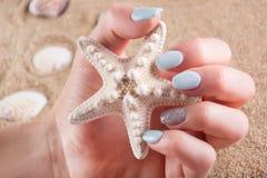 Dziewczyna z błękitną manicure gwoździ połysku mienia rozgwiazdą w ręce fotografia stock
