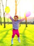 Dziewczyna z balonów skakać plenerowy, przy zmierzchem Zdjęcie Stock