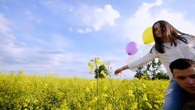 Dziewczyna z balonami na ramionach faceta bieg w śródpolnym gwałcie zdjęcie wideo