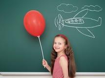 Dziewczyna z balonowym rysunku samolotem na zarządzie szkoły Obrazy Royalty Free