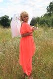 Dziewczyna z białym parasolem, długa suknia, pole kwiaty, różowi suknię piękna blondynki dziewczyna w polu kwiaty zdjęcie stock