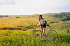 Dziewczyna z bicyklem bierze odpoczynek w pięknym wiejskim krajobrazie obrazy royalty free