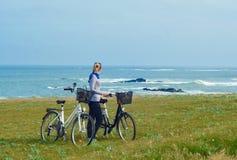 Dziewczyna z bicykli/lów spojrzeniami przy oceanem zdjęcie royalty free