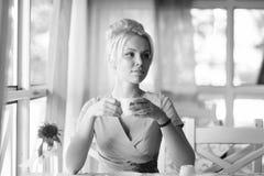 Dziewczyna z blondynem w babeczce na bławym cukiernianym tle Dama w klasyk sukni i otwiera twarz chwytów filiżankę zdjęcia stock