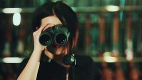 Dziewczyna z brown włosiany patrzeć przez lornetek zdjęcie wideo