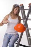 Dziewczyna z budynku hełmem na drabinie Zdjęcia Stock