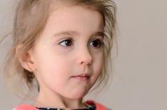 Dziewczyna z bufiastymi policzkami, brązów oczami i długim powiek pensively lo, zdjęcie royalty free