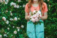 Dziewczyna z bukietem różowe róże na tle róża krzak obraz royalty free