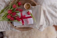 Dziewczyna z bukietem tulbpans na kanapie w domu Prezent na Macierzystym ` s dniu Przyjemna niespodzianka Kobieta w izbowym inter obrazy royalty free