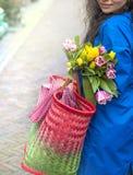 Dziewczyna z bukietem wiosna tulipany w menchiach W błękitnym deszczowu i kolorów żółtych butach na ulicie w Europa szczęśliwa ko zdjęcia royalty free