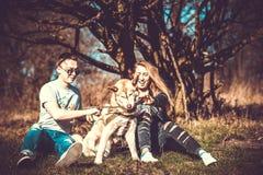 Dziewczyna z chłopakiem i jej łuskowaty psi plenerowy w lesie Zdjęcia Royalty Free