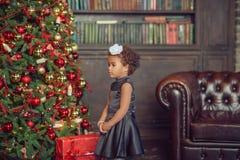 Dziewczyna z ciemnego włosy pozycją na pudełku z prezentami Święta moje portfolio drzewna wersja nosicieli obrazy stock