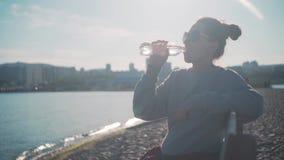 Dziewczyna z ciemnym włosy w bluzie sportowej i szkłach siedzi na ławce i napój wodzie od plastikowej butelki blisko morza zbiory wideo