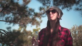 Dziewczyna z ciemnym włosy w czarnej i czerwonej koszula, bandana stojaki w napój wodzie od plastikowej butelki i lesie zbiory wideo