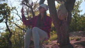 Dziewczyna z ciemnym włosy w czarnej i czerwonej koszula, bandany i szkła siedzi w lesie, bierze fotografię na telefonie zbiory wideo
