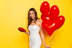 Dziewczyna z czerwień balonami otrzymywającymi od jej chłopaka na walentynki ` s dniu cukierkami i Fotografia Stock
