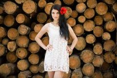 Dziewczyna z czerwonym kwiatem w jej włosy w bielu smokingowy pozować przeciw tłu bele i zdjęcie stock