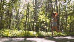 Dziewczyna z czerwonym włosy na bieg w lasowej Pięknej sportsmence na szkoleniu plenerowym swobodny ruch zbiory