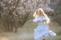Dziewczyna z długim kędzierzawym blondynem Tanczyć w kwitnie ogródzie czysta natura obrazy stock