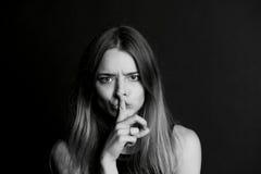 Dziewczyna z długie włosy chwytami dotyka blisko warg gest cisza, sekretność, sekret fotografia stock