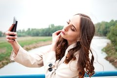 Dziewczyna z długie włosy i kędziory w pozyci na su sukni i żakieta Obrazy Stock