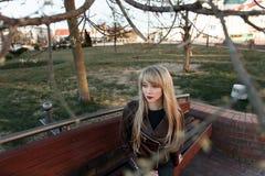 Dziewczyna z długie włosy na ławce w parku zdjęcia royalty free